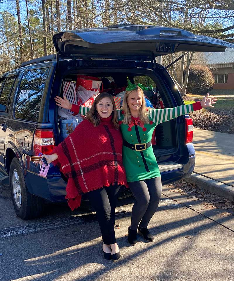 Sydney Hardy and Erin Creech delivering gifts to the school