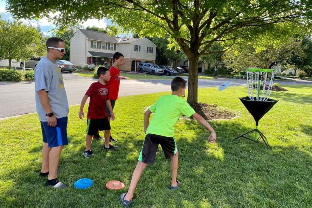Josh Golomb and his three sons playing disc golf.