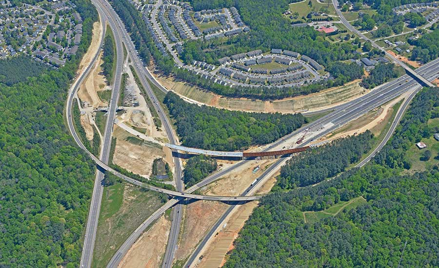 This aerial photo of the Interstate 40-440 interchange shows the old set of bridges in the outer perimeter, with the new flyover structure shown under construction above.
